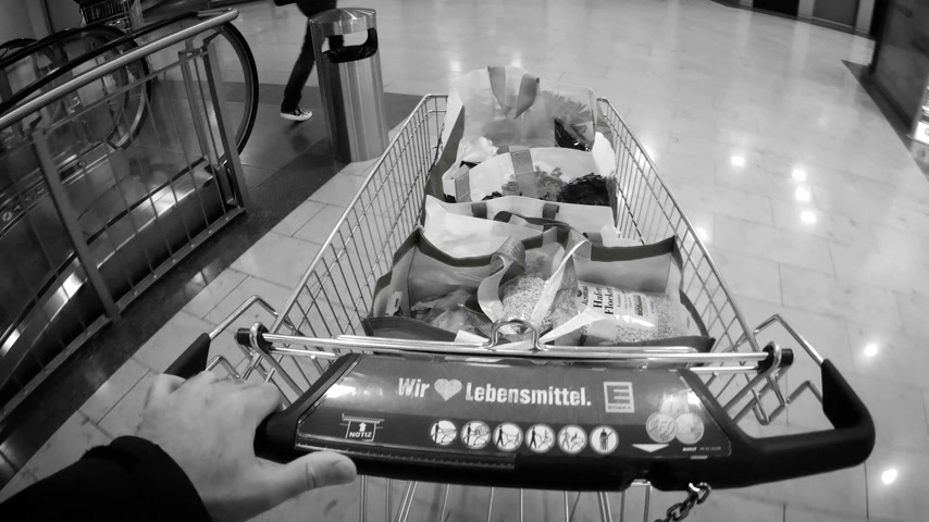 caixa : FRANKFURT, GERMANY - CIRCA 2017: Male pushing supermarket cart in retail place full with food bought from Edeka supermarket retail in German city in black and white