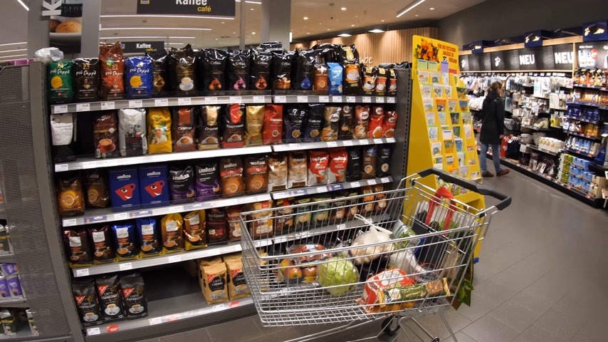 admirado : FRANKFURT, GERMANY - CIRCA 2017: Edeka German supermarket with Coffee stand and Tchibo product being admired by woman customer