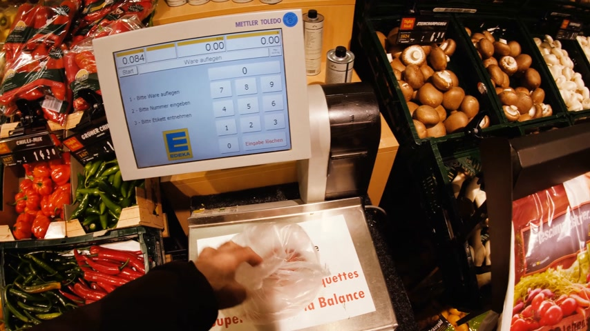 koszyk zakupy : FRANKFURT, GERMANY - CIRCA 2017: Male point of view at supermarket shopping for vegetables and fruits using electronic scale to weigh the tomatoes