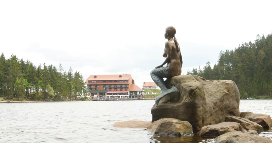 arquipélago : Mummelsee, Germany - Circa 2017: Mermaid statue over the lake of Mummelsee western mountainside of the Hornisgrinde in the Northern Black Forest of Germany. It is very popular with tourists travelling along the Schwarzwaldhochstrasse