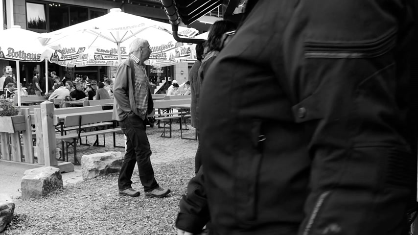 отправка почтой : Mummelsee, Germany - Circa 2017: Tourist having walking in slow motion slomo near open food terrace with main focus on the postal box by Deutsche Post  black and white