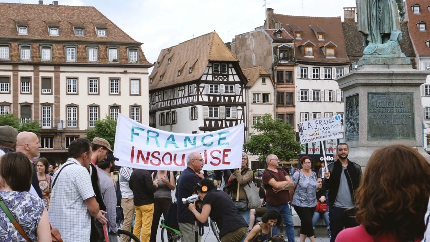 protestor : STRASBOURG, FRANCE - JUL 12, 2017: France Insoumise placard at protest Place Kleber against Macron government spending cuts and pro-business tax and labor reforms