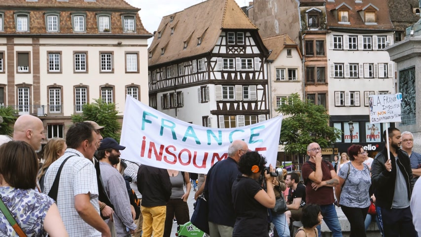 protestor : STRASBOURG, FRANCE - JUL 12, 2017: France Insoumise placard at protest Place General Kleber against Macron government spending cuts and pro-business tax and labor reforms