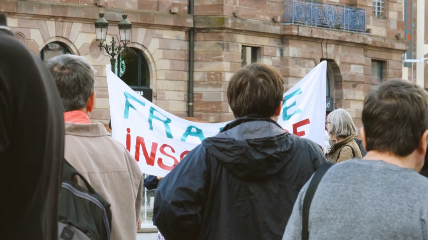 protestor : STRASBOURG, FRANCE - JUL 12, 2017: France Insoumise placard at protest against Macron government spending cuts and pro-business tax and labor reforms Stock Footage