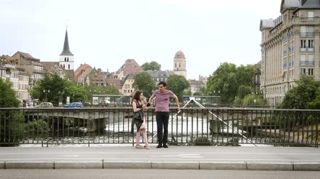 strasburg : Strasbourg, France - Circa 2017: Young couple with smoking male on the Pont dAuvergne in central Strasbourg talking about the future plans to visiting the city travel to Alsace Strasbourg France