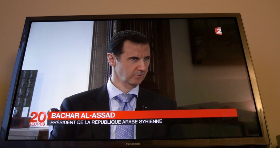haber : PARIS, FRANCE - APR 20, 2015: Interview of Syrian President Bashar al-Assad to David Pujadas from France TV on TV screen in living room on evening news special edition Stok Video