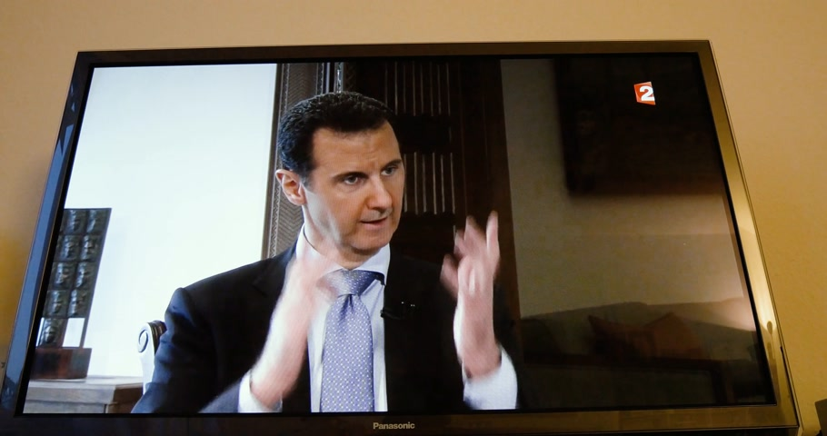 french president : PARIS, FRANCE - APR 20, 2015: Time-lapse fast motion of interview of Syrian President Bashar al-Assad to David Pujadas from France TV on TV screen in living room on evening news special edition Stock Footage
