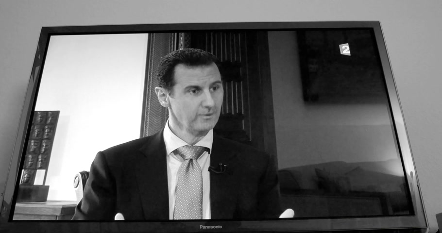 isis : PARIS, FRANCE - APR 20, 2015: Interview of Syrian President Bashar al-Assad to David Pujadas from France TV on TV screen in living room on evening news special edition black and white