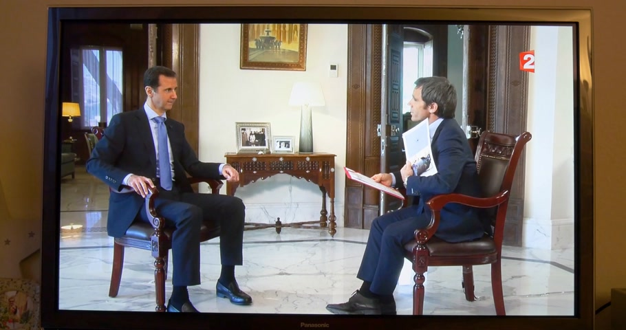 isis : PARIS, FRANCE - APR 20, 2015: Interview of Syrian President Bashar al-Assad to David Pujadas from France  TV asking about bombs and helicopters -  on TV screen in living room