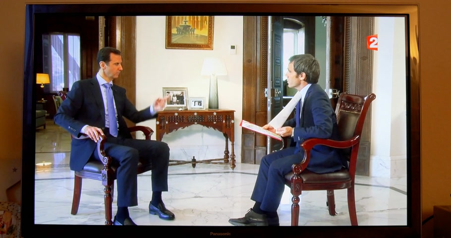 french president : PARIS, FRANCE - APR 20, 2015: Interview of Syrian President Bashar al-Assad to David Pujadas from France  TV asking about bombs and helicopters -  on TV screen in living room