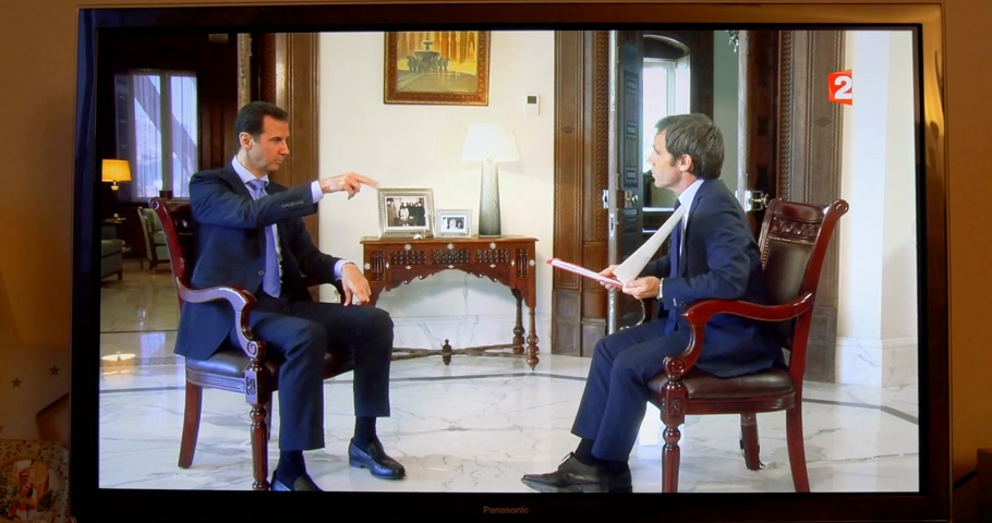 french president : PARIS, FRANCE - APR 20, 2015: Living room tv news Interview of Syrian President Bashar al-Assad to David Pujadas from France 2 TV asking about bombs and helicopters - Bashar explaining