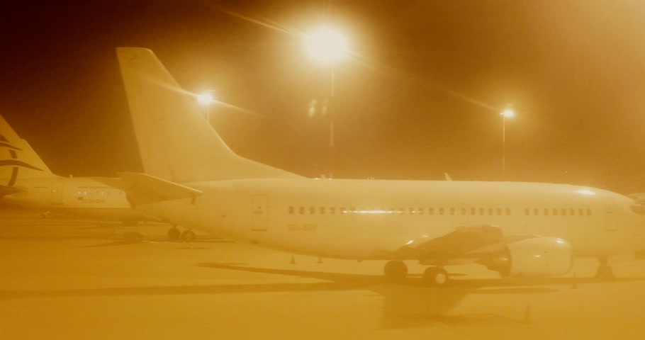 tarmac : ATHENS, GREECE - CIRCA 2017: Fog night motion at airport tarmac at night motion at the Athens international Airport with multiple Boeing and Airbus aircraft from Aegean Airlines