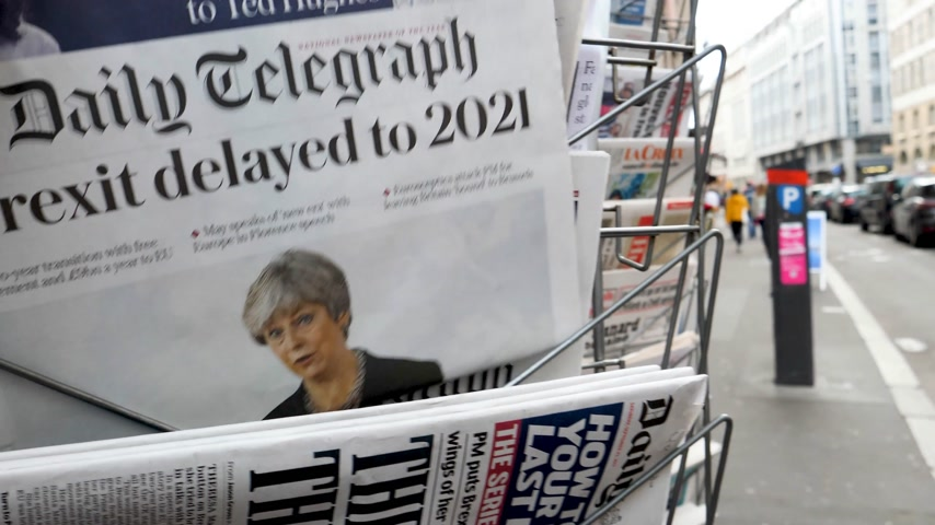 brexit : PARIS, FRANCE - SEP 23, 2017: Man buying latest The Daily Telegraph newspaper from press kiosk with Braking news from Theresa May British Prime Minister Brexit delayed to 2021