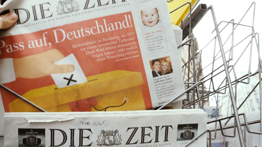 chancellery : PARIS, FRANCE - SEP 23, 2017: Man buying latest newspaper Die Zeit German press with portrait of Angela Merkel before the election in Germany for the Chancellor of Germany, the head of the federal government, currently Angela Merkel