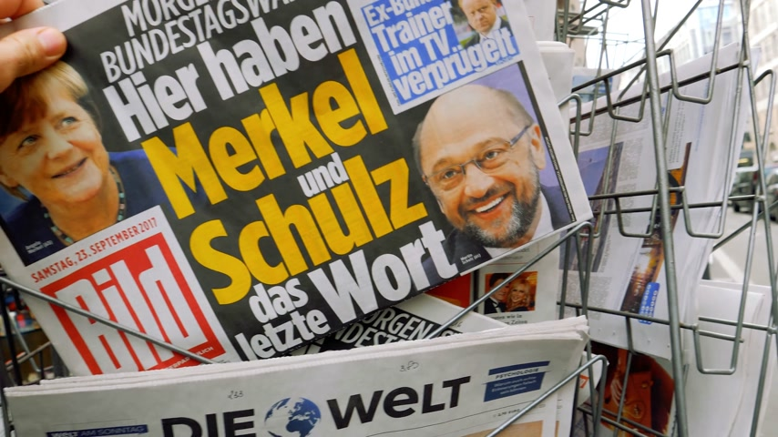 election campaign : PARIS, FRANCE - SEP 23, 2017: Man buying latest newspaper Die Bild with with portrait of Angela Merkel And Martin Schulz before the election in Germany for the Chancellor of Germany, the head of the federal government, currently Angela Merkel