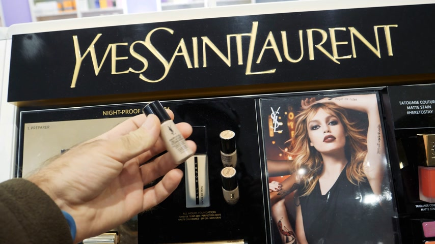 showcase : PARIS, FRANCE - CRICA 2017: Male customer travestite buying Yves Saint Laurent female cosmetics in cosmetics fashion store on Champs Elysee