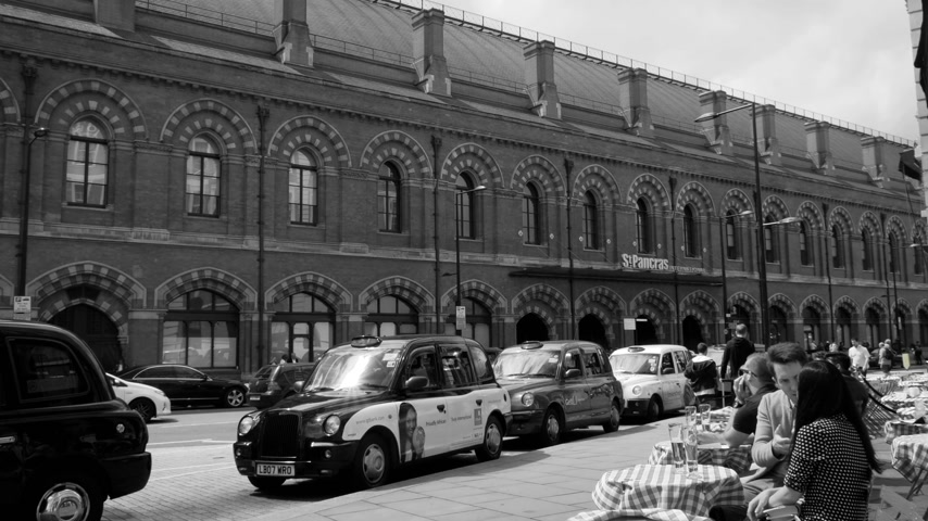 concourse : LONDON, UNITED KINGDOM  - CIRCA 2017: Long row of London Taxi cab hackney carriage parked in front of the St Pancras international Train station in London with customer drinking coffee at outside terrace