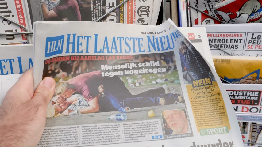 tabloid : PARIS, FRANCE - OCT 3, 2017: Man buying het laatste nieuws newspaper with socking title and photo at press kiosk about the 2017 Las Vegas Strip shooting in United States with about 60 fatalities and 527 injuries