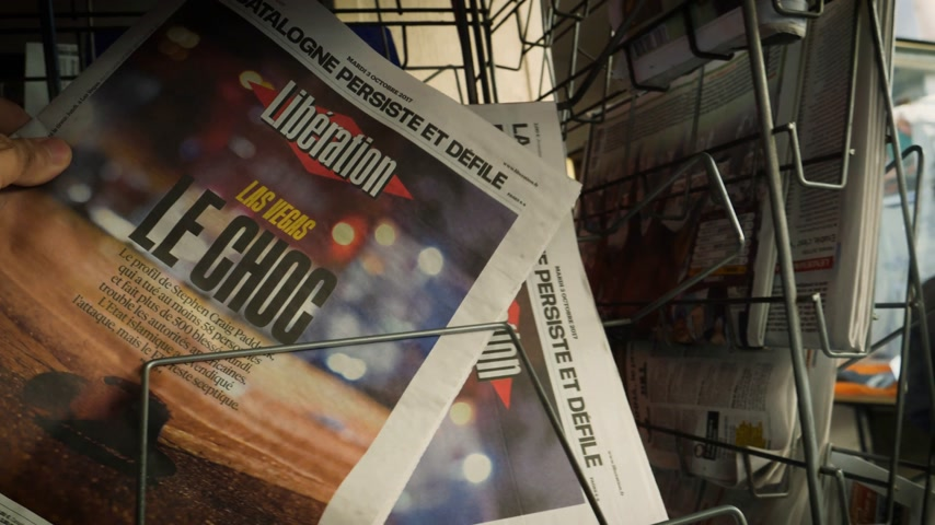 gunman : PARIS, FRANCE - OCT 3, 2017: Man buying Liberation French newspaper with socking title and photo at press kiosk about the 2017 Las Vegas Strip shooting in United States with about 60 fatalities and 527 injuries