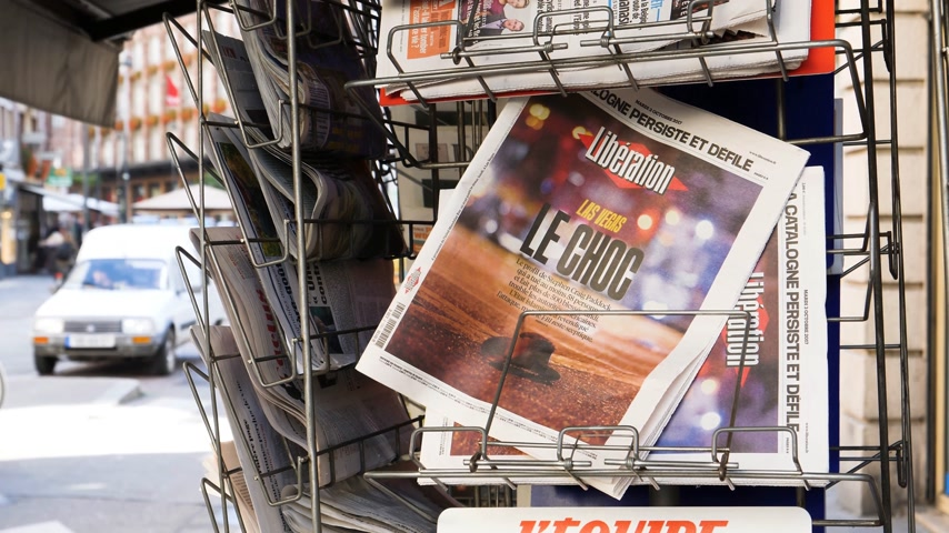 mass shooting : PARIS, FRANCE - OCT 3, 2017: Liberation French newspaper with socking title and photo at press kiosk about the 2017 Las Vegas Strip shooting in United States with about 60 fatalities and 527 injuries Stock Footage