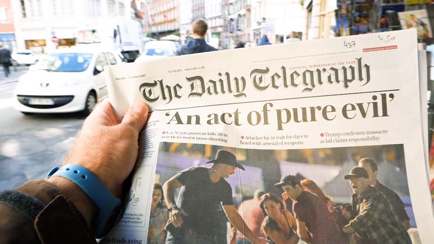 журналистика : PARIS, FRANCE - OCT 3, 2017: Man buying The Daily Telegraph newspaper with socking title Pure Evil and photo at press kiosk about the 2017 Las Vegas Strip shooting in United States slow motion