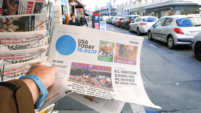 felvonás : PARIS, FRANCE - OCT 3, 2017: Man reading USA TODAY newspaper with socking title Pure Evil and photo at press kiosk about the 2017 Las Vegas Strip shooting in United States with about 60 kills slow motion