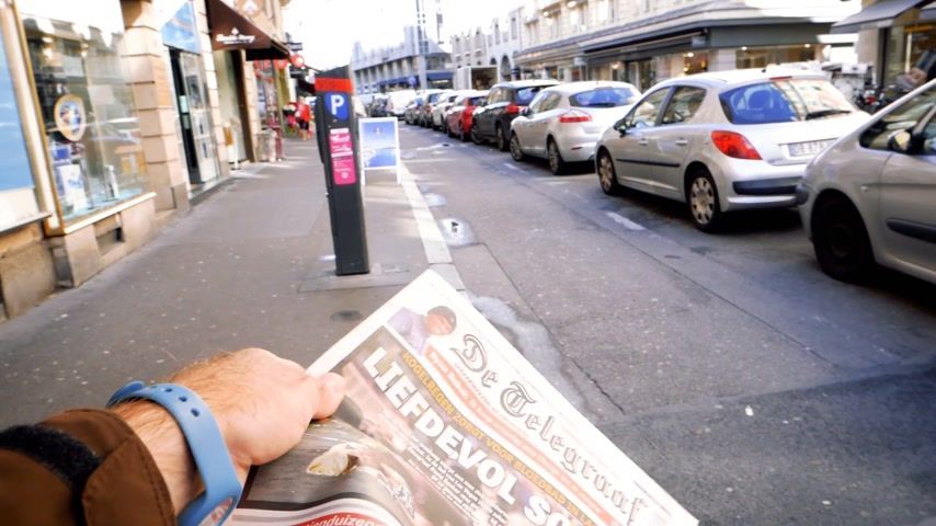 buy newspaper : PARIS, FRANCE - OCT 3, 2017: Man reading De Telegraaf newspaper with socking title and photo at press kiosk about the 2017 Las Vegas Strip shooting in United States  slow motion Stock Footage