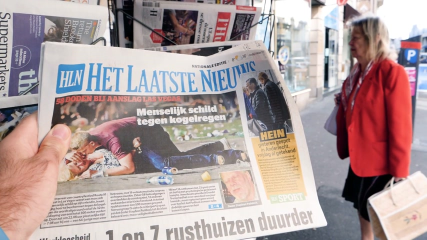 mass shooting : PARIS, FRANCE - OCT 3, 2017: Man reading het laatste nieuws newspaper with socking title and photo at press kiosk about the 2017 Las Vegas Strip shooting in United States 60 fatalities - slow motion Stock Footage