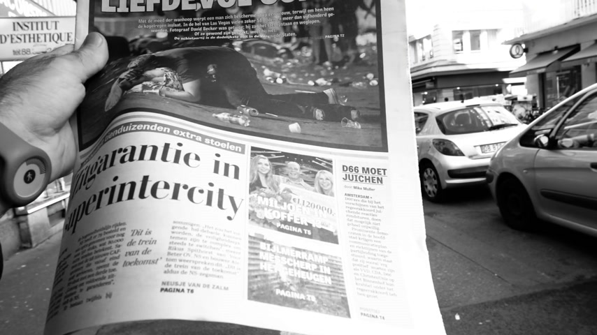 buy newspaper : PARIS, FRANCE - OCT 3, 2017: Man reading De Telegraaf newspaper with socking title and photo at press kiosk about the 2017 Las Vegas Strip shooting in United States  slow motion black and white