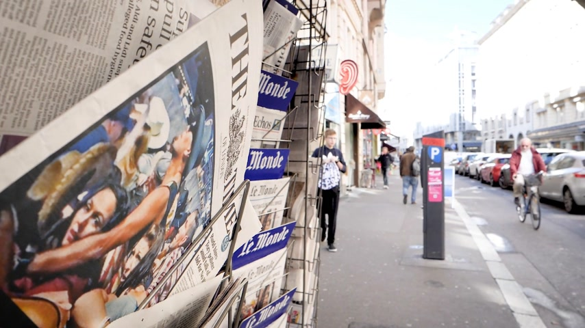 tabloid : PARIS, FRANCE - OCT 3, 2017: Pedestrians near the Times newspaper with socking title and photo at press kiosk about the 2017 Las Vegas Strip shooting in United States slow-motion city news