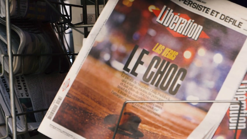 mass shooting : PARIS, FRANCE - OCT 3, 2017: Zoom out from Liberation French newspaper with socking title and photo at press kiosk about the 2017 Las Vegas Strip shooting in United States slow motion Stock Footage