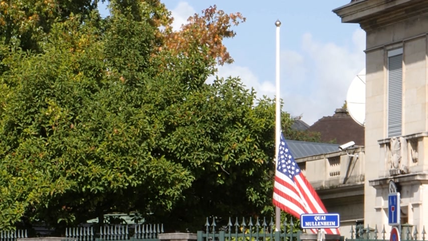 mass shooting : STRASBOURG, FRANCE - OCT 3, 2017: US United States American Flag flying half-mast in court of the US Embassy after 2017 Las Vegas Strip shooting in United States with 60 fatalities and 527 injuries Stock Footage