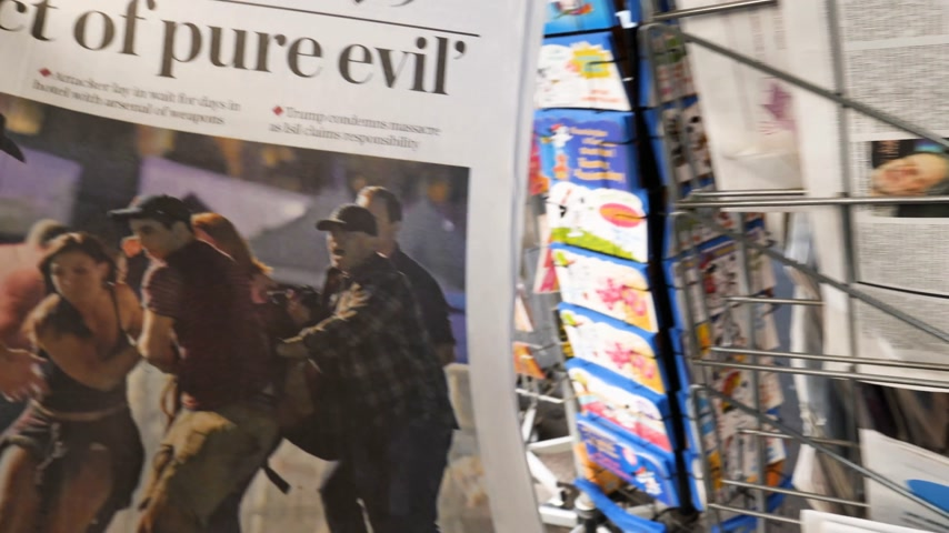 buy newspaper : PARIS, FRANCE - OCT 3, 2017: Man buying The Daily Telegraph newspaper with socking title Pure Evil and photo at press kiosk about the 2017 Las Vegas Strip shooting in United States with about 60 fatalities and 527 injuries