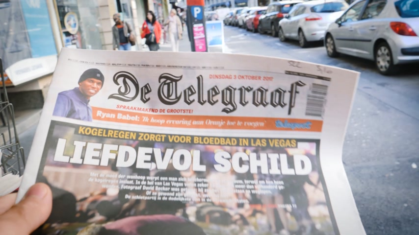 gunman : PARIS, FRANCE - OCT 3, 2017: Man buying De Telegraaf newspaper with socking title and photo at press kiosk about the 2017 Las Vegas Strip shooting in United States with about 60 fatalities and 527 injuries