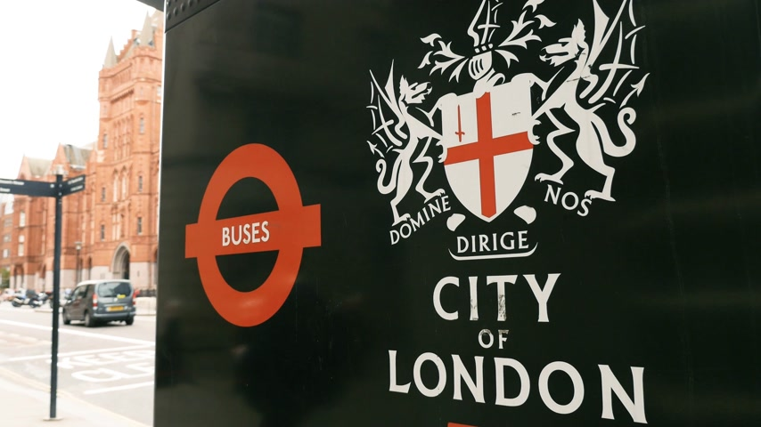 hackney carriage : London, United Kingdom - Circa 2017: Domine Nos Dirige signage on the coat of arms City of London transport bus station with silhouettes of pedestrians in the background, busses, cars