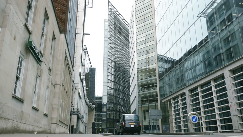 hackney carriage : London, United Kingdom - Circa 2017: View from below of New Fetter Ln lane street  big office skyscraper buildings London traditional taxi driving fast on a working day with empty street cinematic Stock Footage