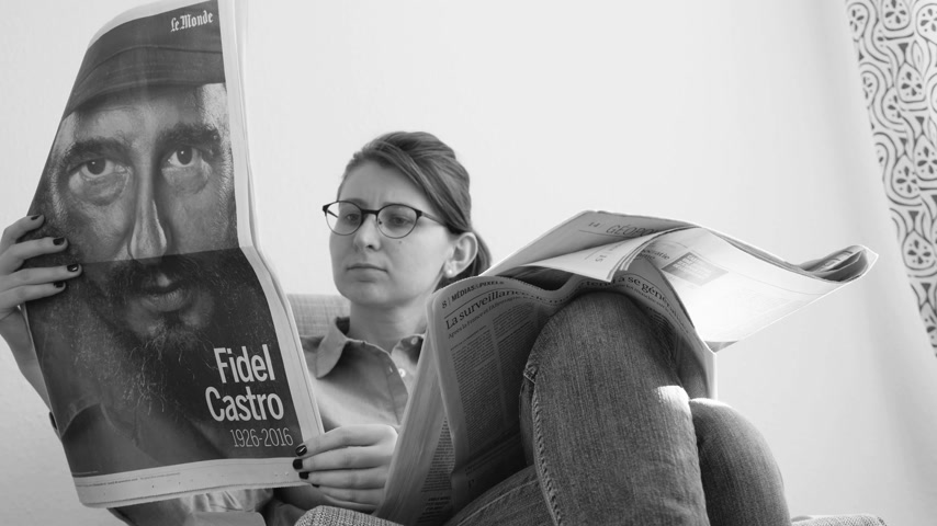 french media : PARIS, FRANCE - NOV 29, 2016: Black and white of curious woman reading Le Monde newspaper with headline and articles about Fidel Castro, Cuban President - dead on November 25, 2016