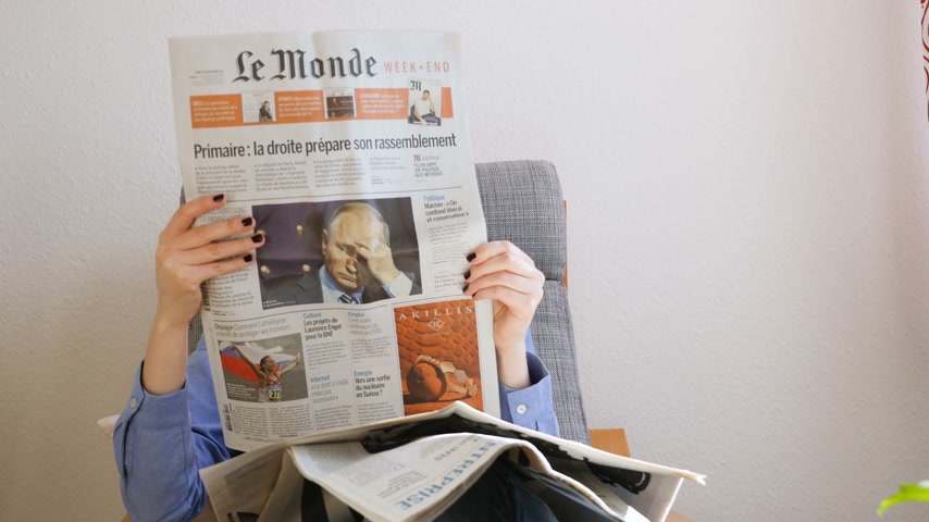 french president : Paris, France - Circa 2017: Woman reading le Monde French newspaper featuring Vladimir Putin Russian Federation president on the first page