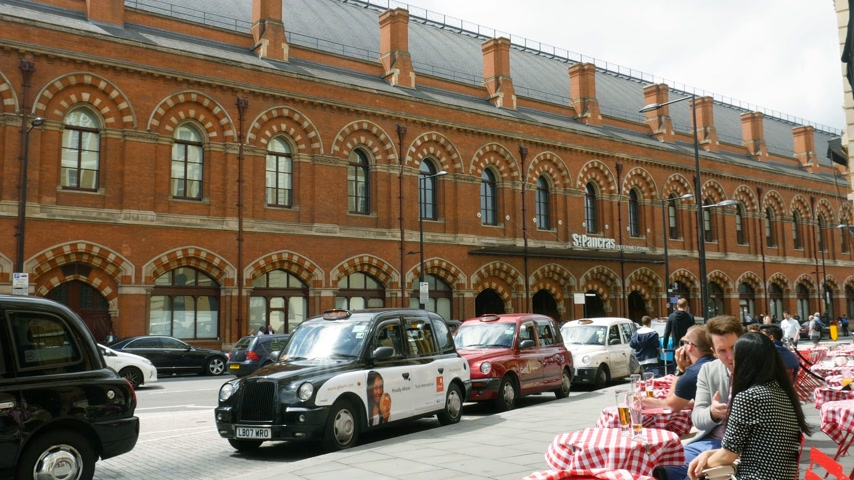 hackney carriage : LONDON, UNITED KINGDOM  - CIRCA 2017: Long row of London Taxi cab hackney carriage parked in front of the St Pancras international Train station in London with customer drinking coffee at outside terrace