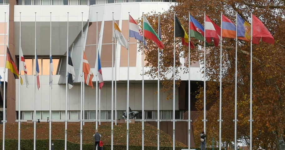 saygı : STRASBOURG, FRANCE - 14 Nov 2015: Tele-lens view of workers of Council of Europe put all European Union Flags at half-mast in front Council of Europe following terrorist attack in Paris at Bataclan
