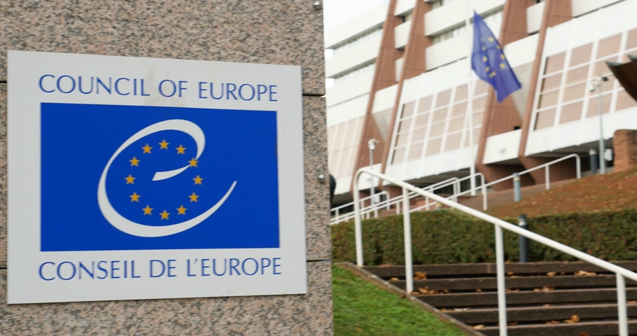 saygı : STRASBOURG, FRANCE - 14 Nov 2015: Pan from Council of Europe logo to the European Union Flag at half-mast at Council of Europe amin entrance  following terrorist attack in Paris at Bataclan