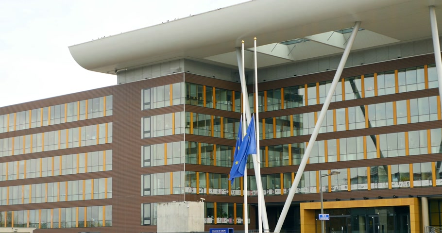 flag half mast : STRASBOURG, FRANCE - NOV 2015: European Union Flag flies at half-mast in front of the Council of Europe Agora building following an terrorist attack in Paris at Bataclan Theatre Stock Footage