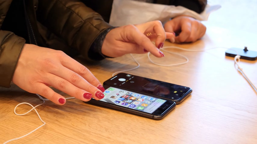 comparar : STRASBOURG, FRANCE - NOV 3, 2017: Woman hands comparing her old iPhone 6 7 8 with new iPhone X 10 on the Apple Store wooden table during launch day Stock Footage