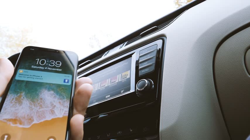 unlocking : Munchen, Germany - Circa 2017: Man connecting his new iPhone X 10 to the navigation system of the car with CarPlay Stock Footage