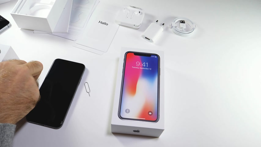alfabeto : PARIS, FRANCE - NOV 3, 2017:  Man POV unboxing of the latest Apple iPhone X 10 smartphone in white studio background removing SIM card from old Se smartphone
