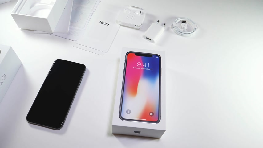 jel : PARIS, FRANCE - NOV 3, 2017:  Man POV unboxing of the latest Apple iPhone X 10 smartphone in white studio background installation of Nano SIM card