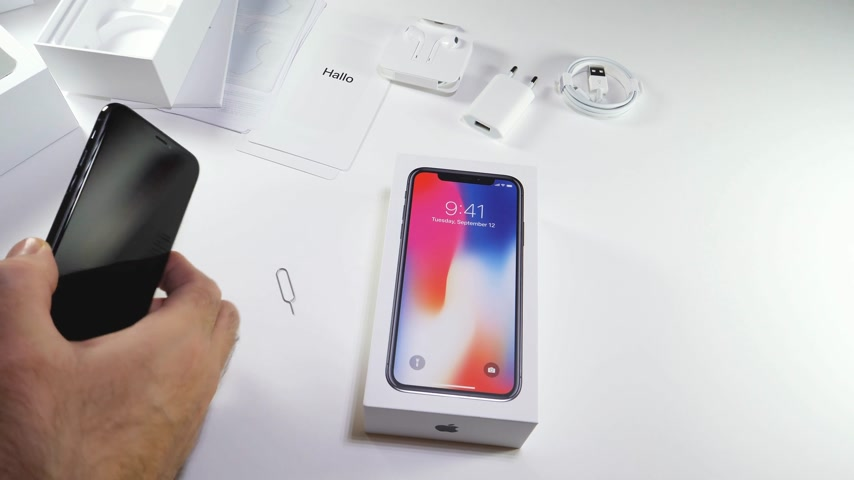 jel : PARIS, FRANCE - NOV 3, 2017:  Man POV unboxing of the latest Apple iPhone X 10 smartphone in white studio background removing SIM card from old Se smartphone
