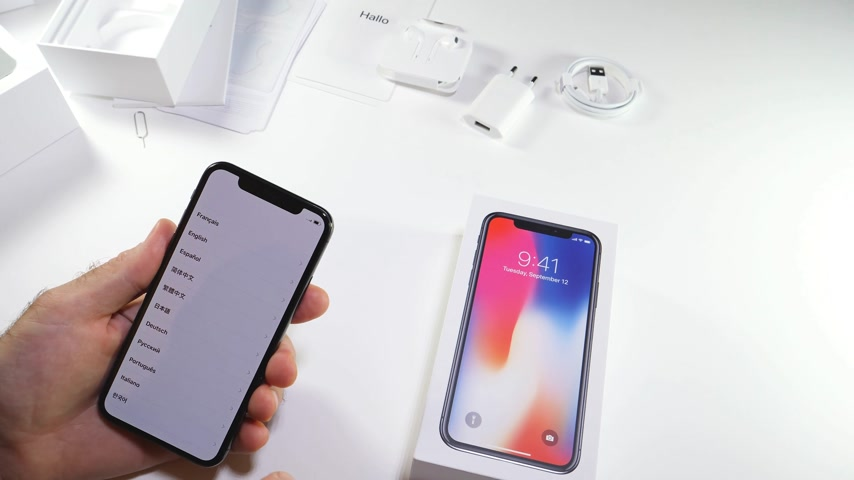 jel : PARIS, FRANCE - NOV 3, 2017:  Man POV unboxing of the latest Apple iPhone X 10 smartphone in white studio background selecting language and country menu