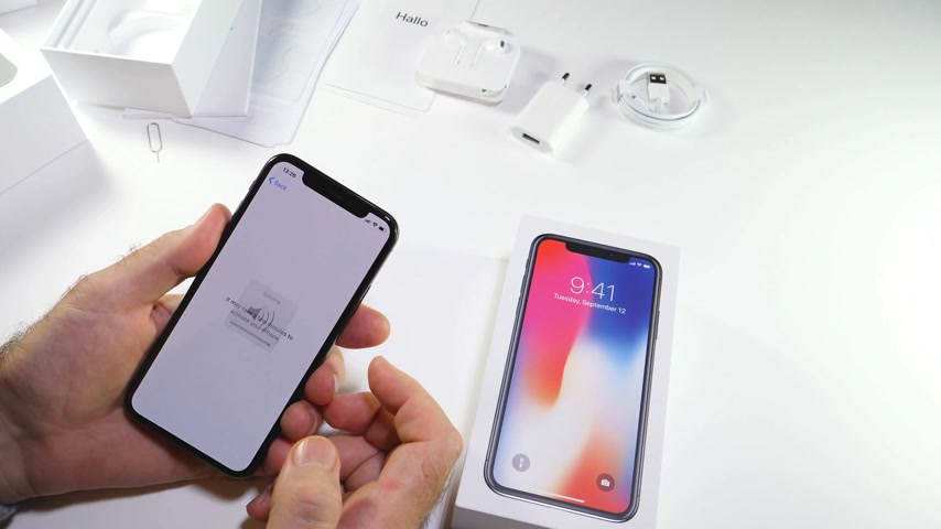 osm : PARIS, FRANCE - NOV 3, 2017:  Man POV unboxing of the latest Apple iPhone X 10 smartphone in white studio background selecting code and face id