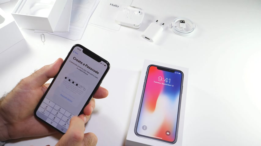 jel : PARIS, FRANCE - NOV 3, 2017:  Man POV unboxing of the latest Apple iPhone X 10 smartphone in white studio background selecting creating the passcode icloud restore apps Stock mozgókép